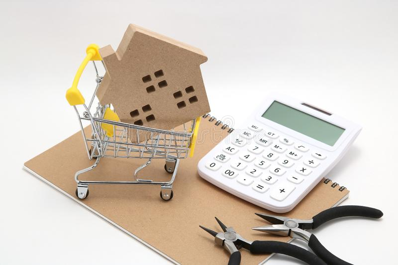 Miniature house, shopping cart, calculator and tools on white background. Concept of buying new house, real estate and renovation. stock image