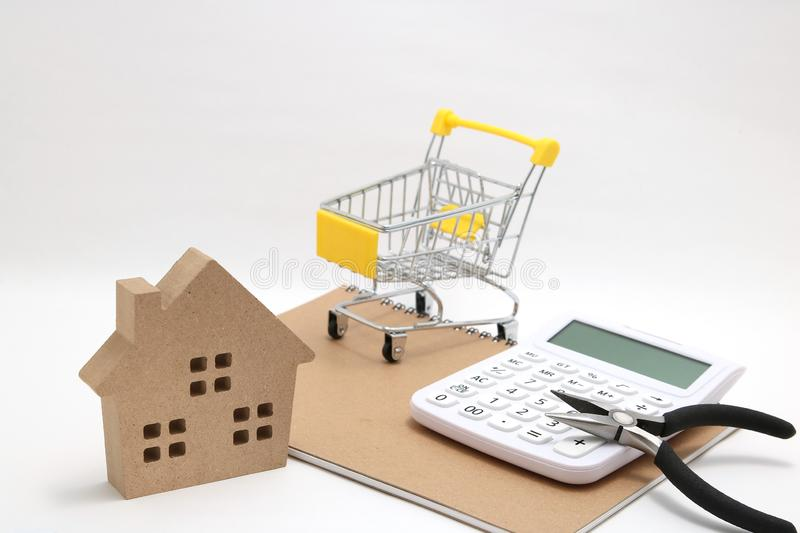 Miniature house, shopping cart, calculator and tools on white background. Concept of buying new house, real estate and renovation. royalty free stock photo