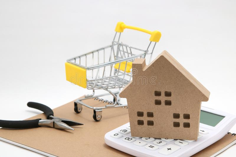 Miniature house, shopping cart, calculator and tools on white background. Concept of buying new house, real estate and renovation. royalty free stock image