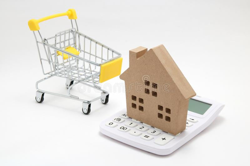 Miniature house, shopping cart and calculator on white background. Concept of buying new house, real estate and home mortgage. stock images