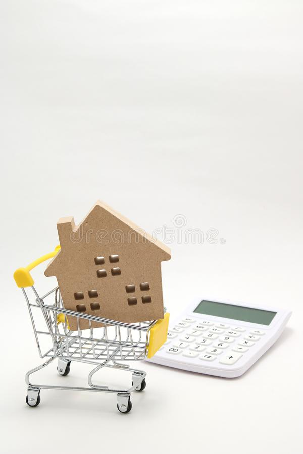 Miniature house, shopping cart and calculator on white background. Concept of buying new house, real estate and home mortgage. royalty free stock images