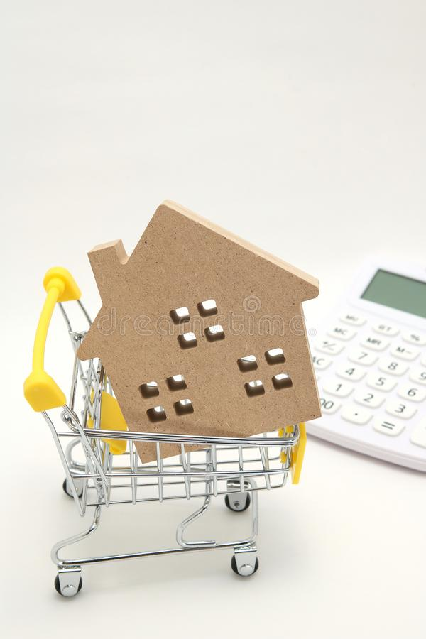 Miniature house, shopping cart and calculator on white background. Concept of buying new house, real estate and home mortgage. stock photography