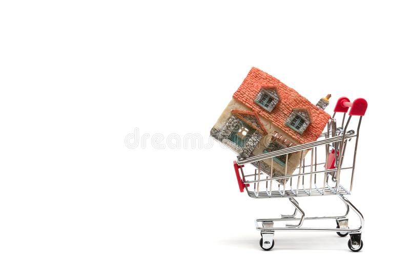 Miniature house and shopping cart on white background : economy royalty free stock photo