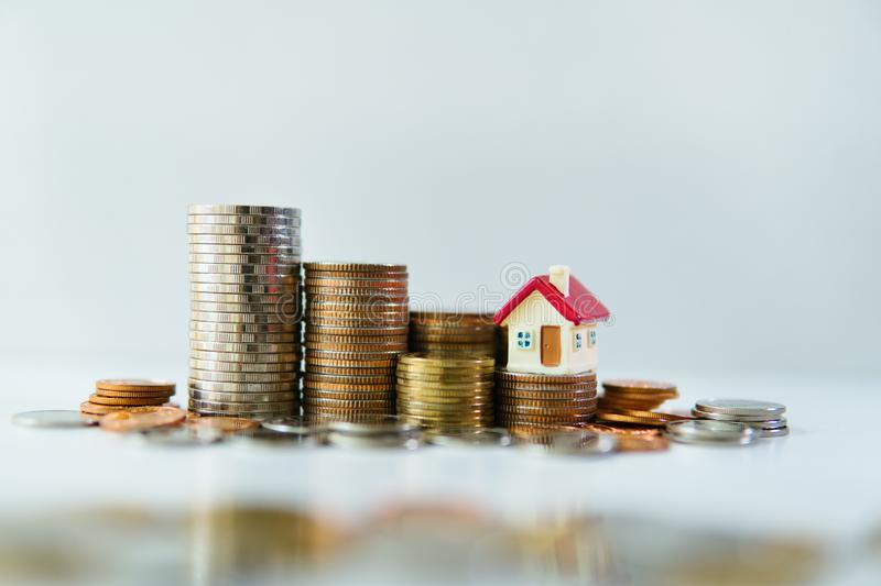 Miniature house on stack coins using as property and business concept. Account, background, banking, cash, copy, space, credit, currency, deposit, development stock photo