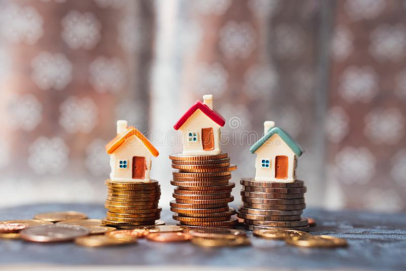 Miniature house on stack coins using as property real estate and financial concept royalty free stock photography