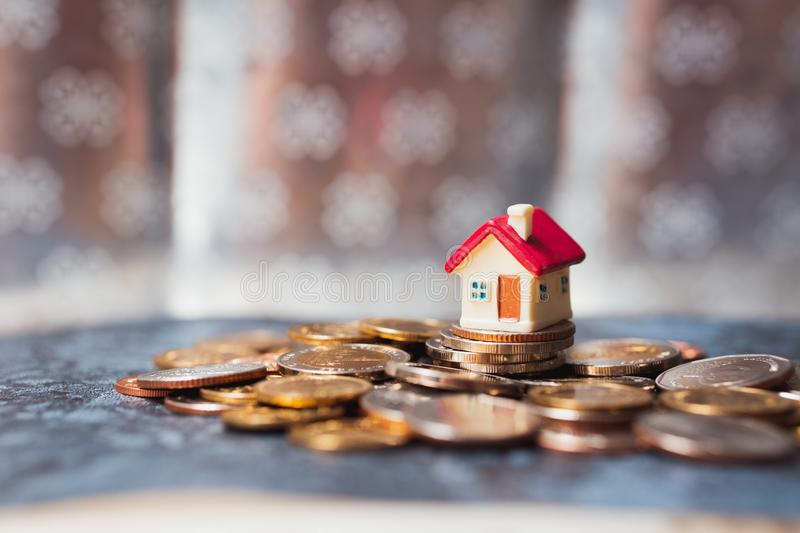 Miniature house on stack coins using as property real estate and financial concept stock photography