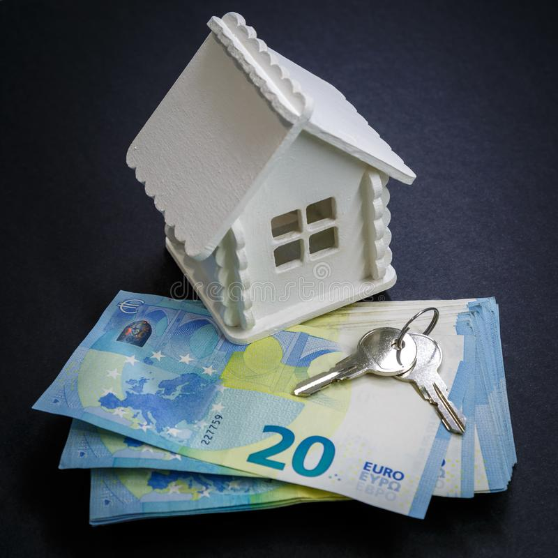 Miniature house of white colour, money and keys as an illustration of the process of buying a home.  stock photos