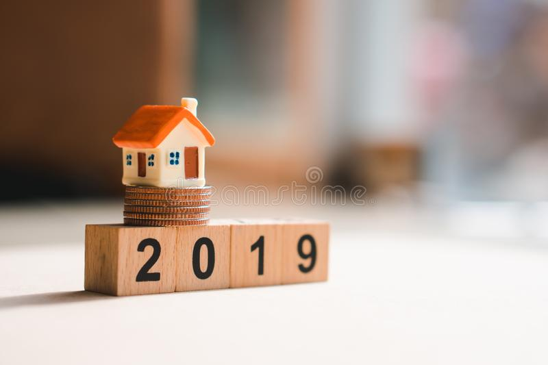 Miniature house on 2019 wooden block with stack coins using as f. Inance and business concept, background, banking, building, calendar, cash, challenge, copy royalty free stock photo