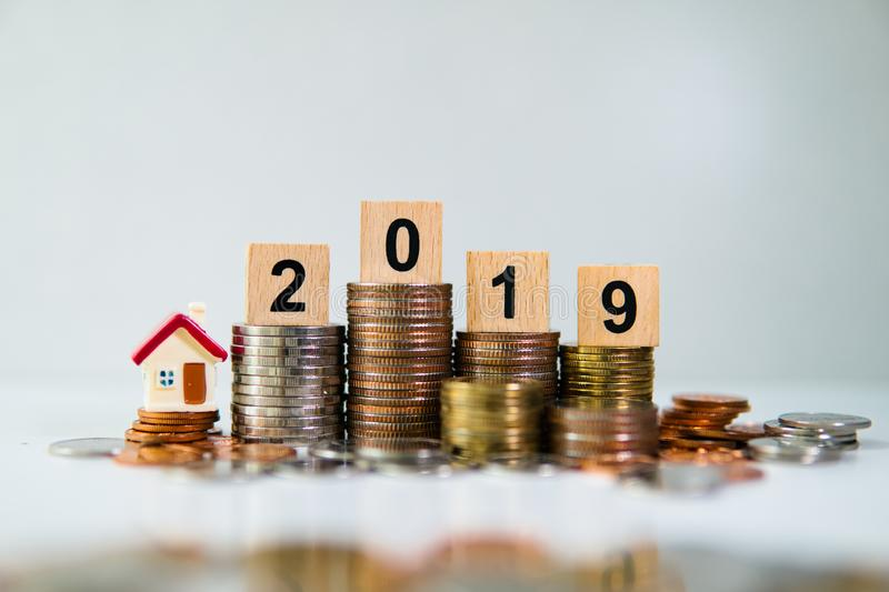 Miniature house on wooden block year 2019. With stack coins using as business and property concept royalty free stock image