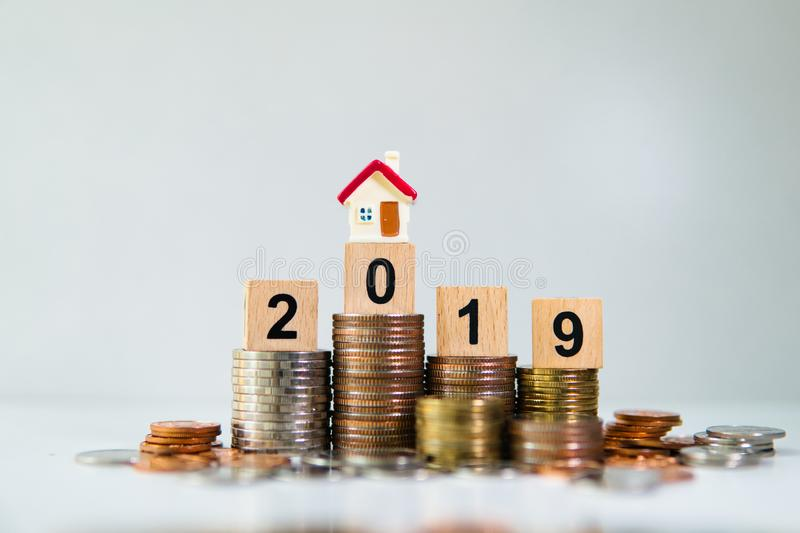 Miniature house on wooden block year 2019 with stack coins. Using as business and property concept stock photo