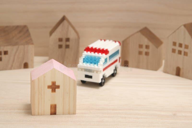 Miniature houses, hospital and ambulance on wood. stock photo