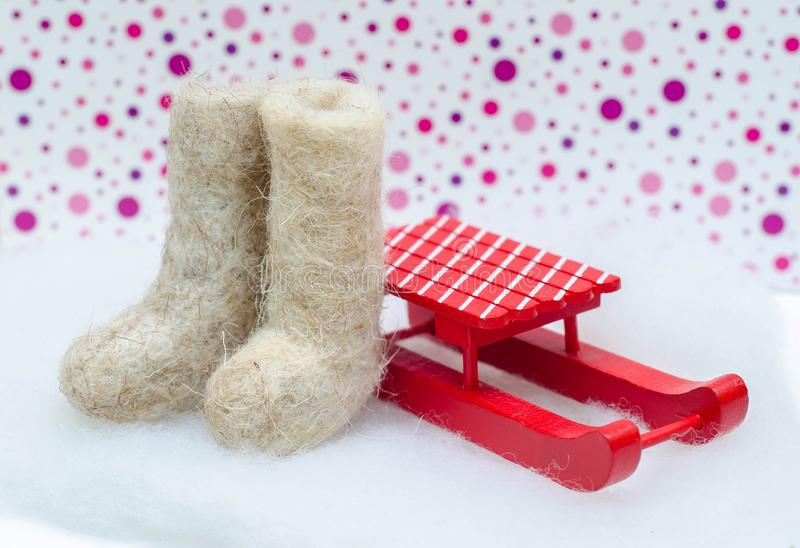 Miniature light felt boots and red sled royalty free stock images