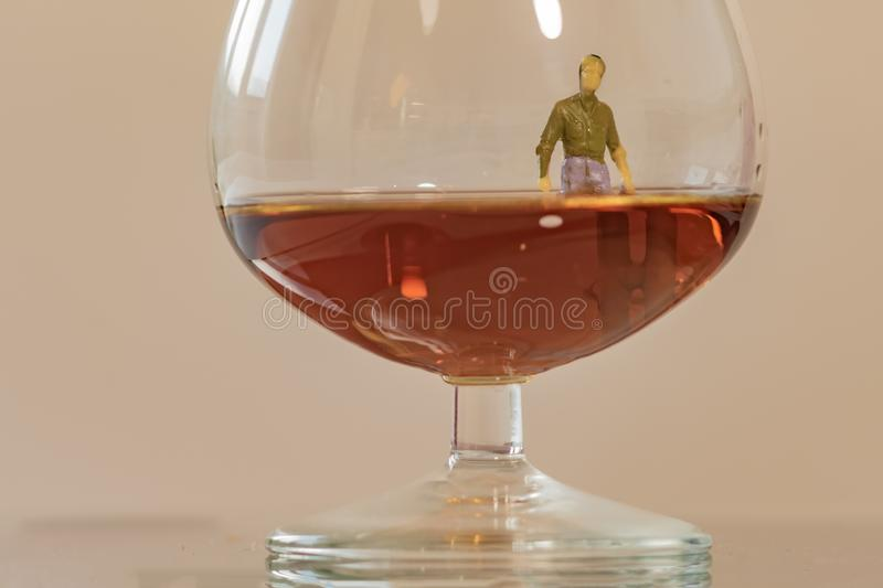 Miniature man figure sinking in the glass of brandy. Shallow depth of field background. Healthcare and alcoholism concept.  royalty free stock photo