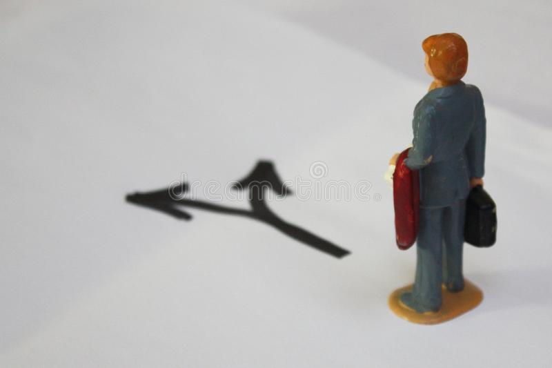 Miniature man thinking, which way to go. Decision making conceptual photo stock images