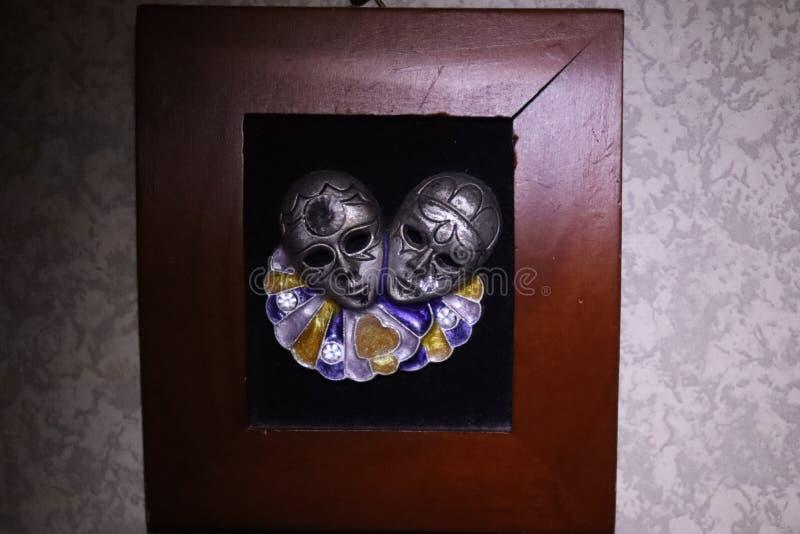Miniature masquerade masks. Pair of miniature masquerade masks in wood frame stock image