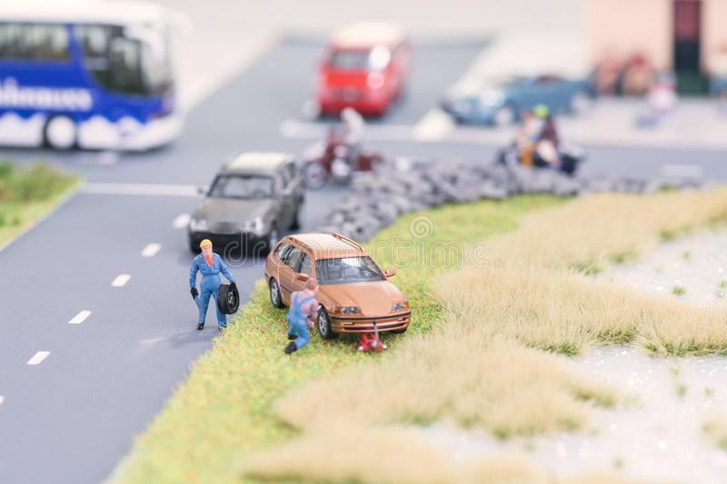 Miniature mechanics replacing a tyre off the roadway. Close-up royalty free stock photography