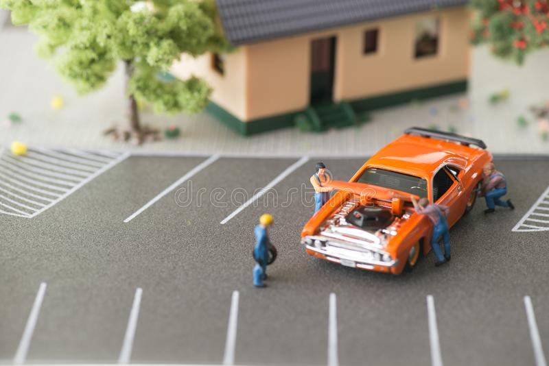 Miniature mechanics working on a car royalty free stock photography