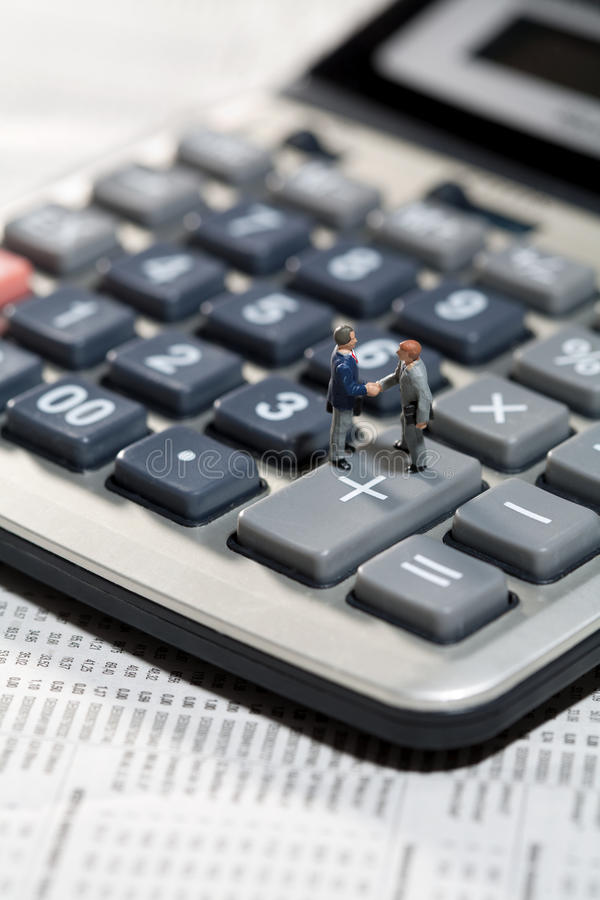 Miniature men shaking hands on a calculator. Miniature toy models of men standing on the keys of a calculator shaking hands on a business agreement or accounting stock photography