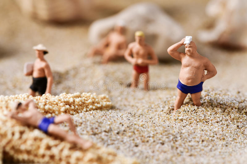 Miniature men in swimsuit on the beach royalty free stock image
