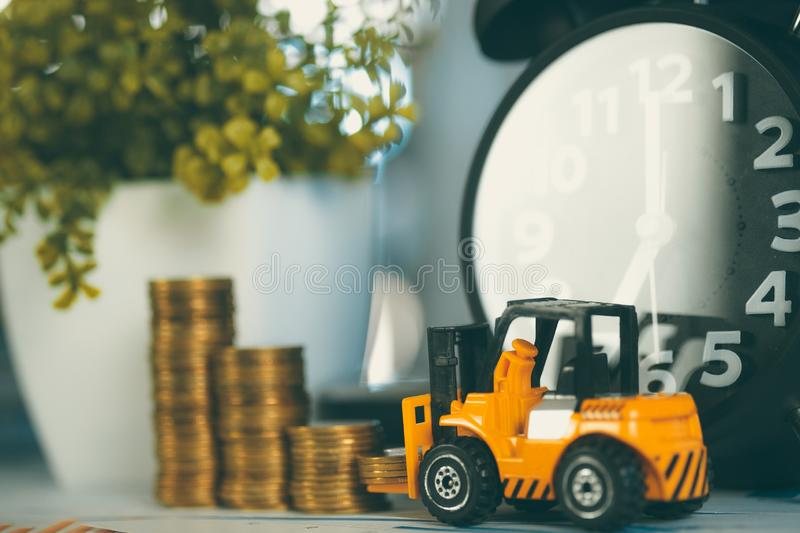 Miniature mini forklift truck with coin stack on working table with office supplies or office work essential tools items royalty free stock photos