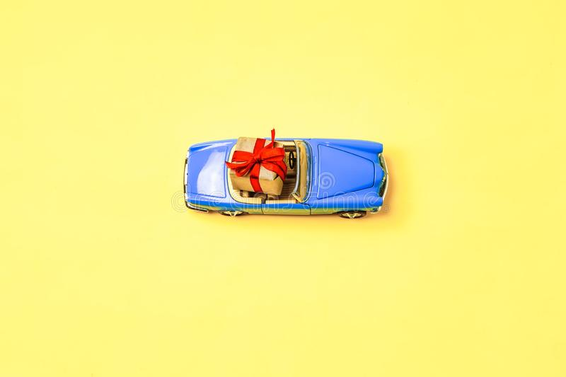 Miniature mini toy.Blue toy car with open top convertible carrying a gift with a red bow on a yellow background. View. From above. Miniature mini toy stock images