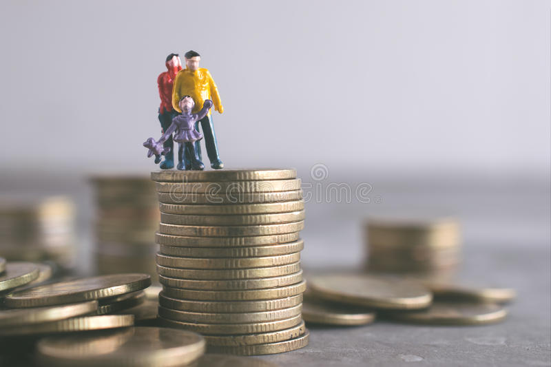 Miniature Mum Dad and Kids standing on top of the money save mon. Ey concept royalty free stock photography