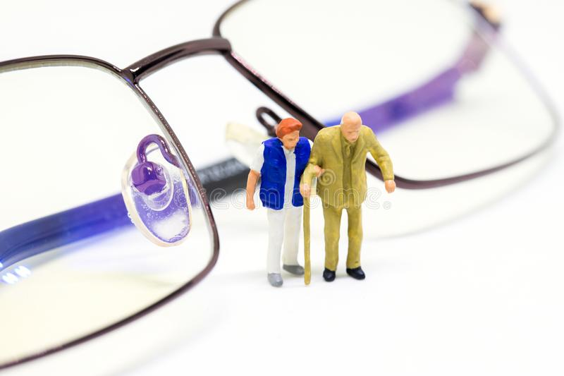 Miniature old couple and optical glasses. Senior age couple walking with support. royalty free stock photos