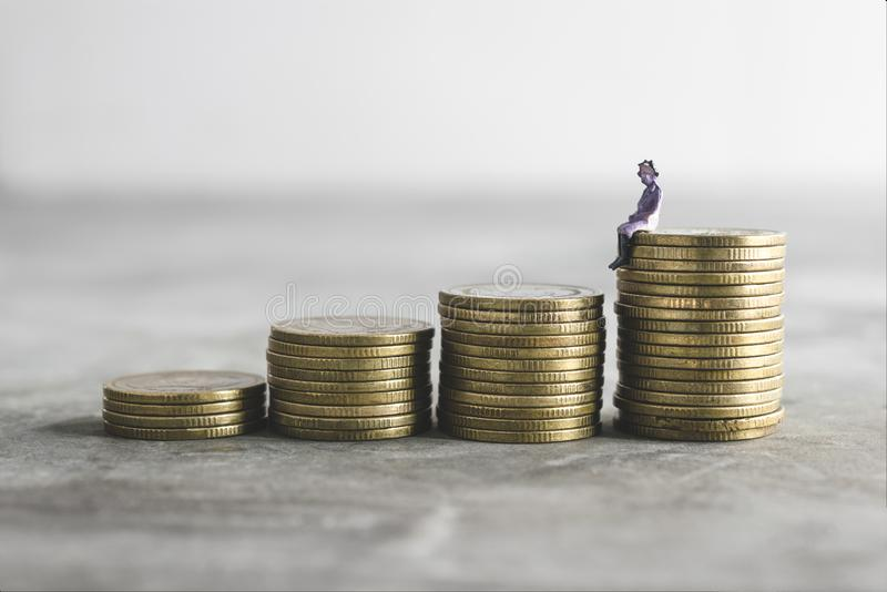 Miniature old lady on top of the money save money concept.  royalty free stock photography
