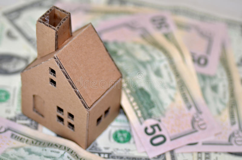 Miniature paper made house stand on money. Paper made house stands on dollar money stock images