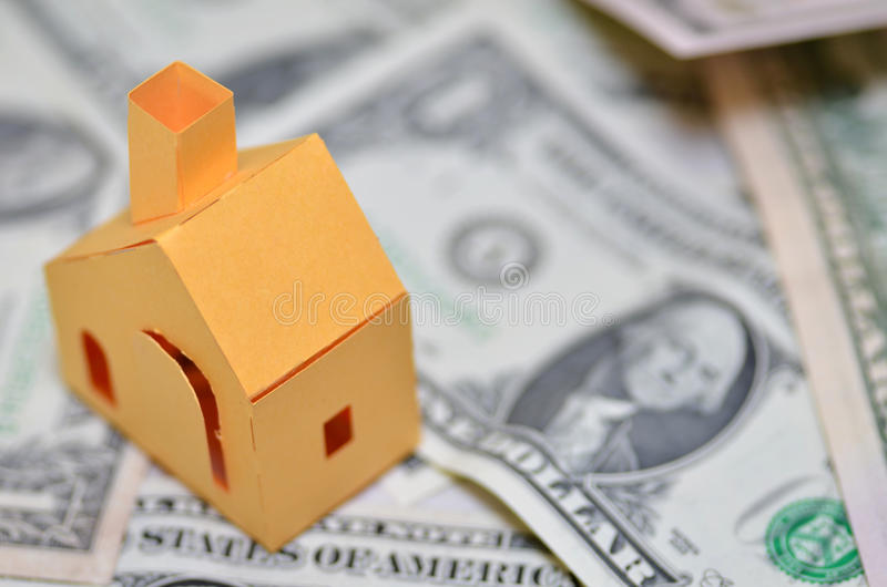 Miniature paper made house stand on money. Paper made house stands on dollar money royalty free stock images