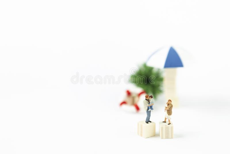 Miniature parents carrying baby over blurred beach object background royalty free stock photography