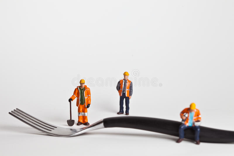 Miniature people in action worker on a fork. Miniature people in action in various situations stock images