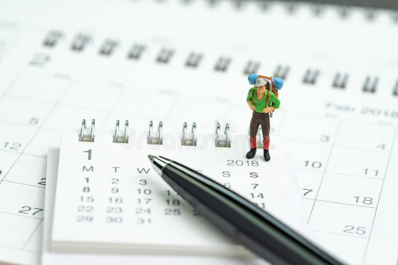 Miniature people, backpacker man figure standing on 2018 calendar with pen using as travel planning, vocation or holiday year plan royalty free stock photos