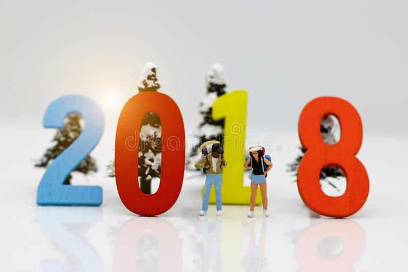 Miniature people, backpackers with word number `2018`. stock photo