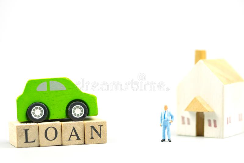 Miniature people : Banker with wood block words LOAN. Home and car stock photo