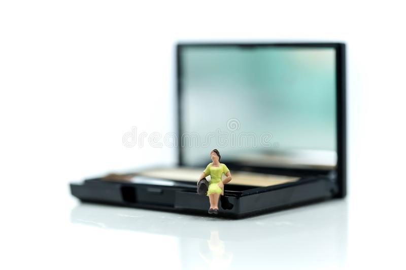 Miniature people : Beautiful womans sitting on makeup products w royalty free stock photos