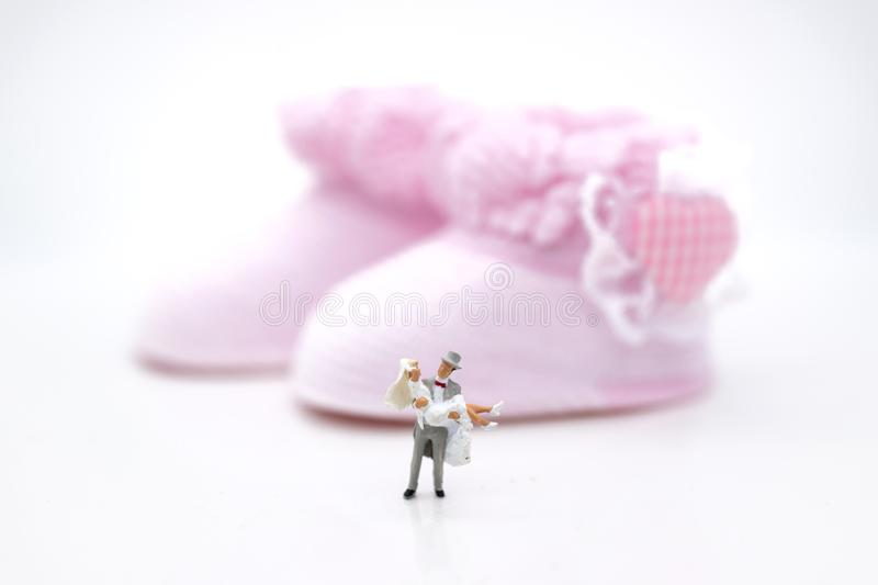 Miniature people : Bride and groom wear wedding suit and waiting for baby in the future . Image use for make new family royalty free stock image