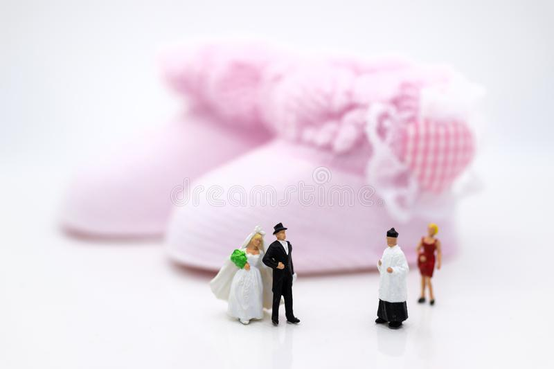 Miniature people : Bride and groom wear wedding suit and waiting for baby in the future . Image use for make new family.  royalty free stock photography