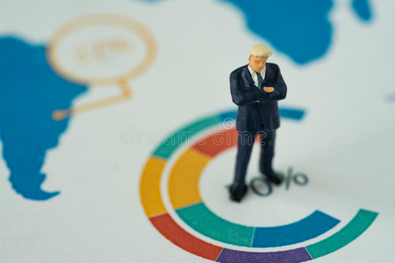 Miniature people business concept as small figure businessmen st. Anding on analysis graph chart stock photography