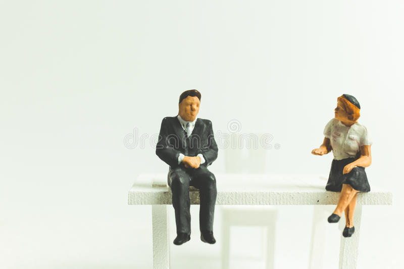 Miniature people business concept sitting on chair with a space stock image