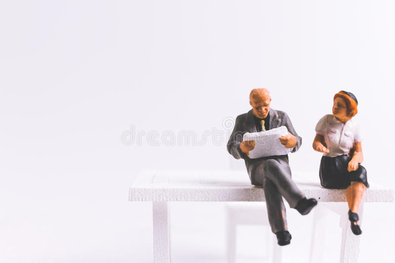 Miniature people business concept sitting on chair with a space royalty free stock images