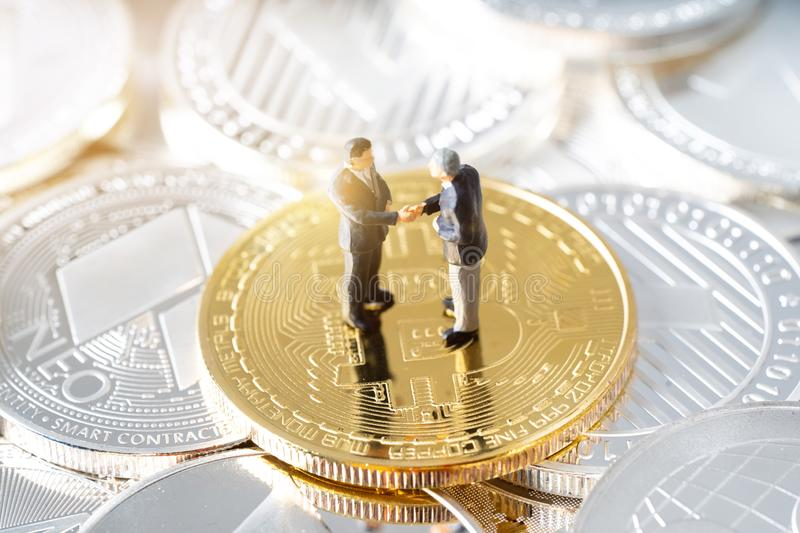 Miniature people business man shaking hands standing on bitcoins coins. Cryptocurrency mining concept royalty free stock images