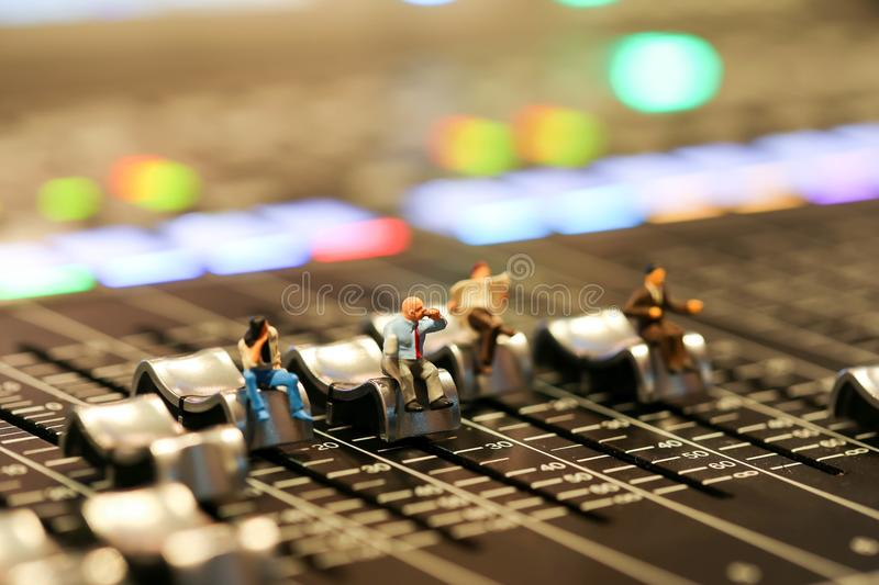 Miniature people : business man sitting on Professional audio mi. Xing console with faders and adjusting knobs,TV equipment ,sound musical mixing&engineering royalty free stock photos