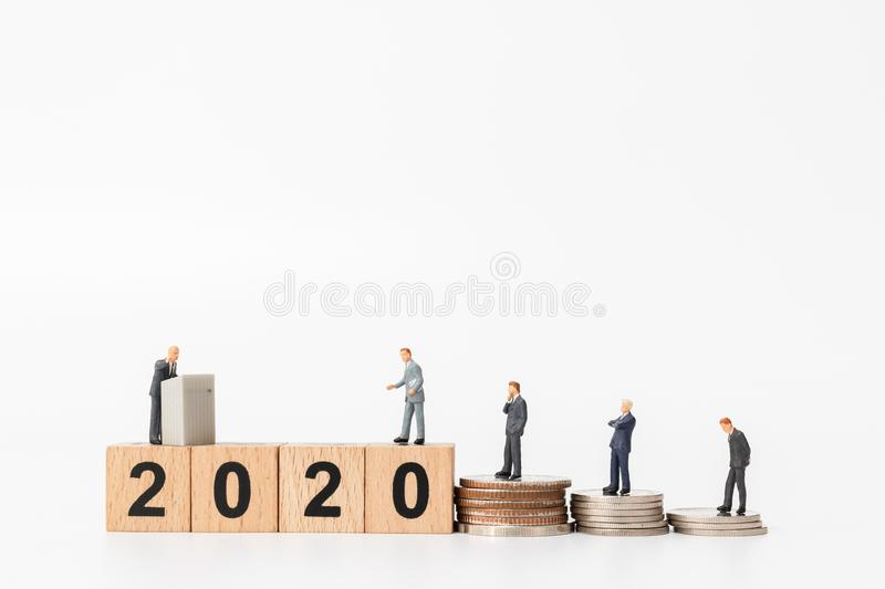 Miniature people : Business people standing on wooden block number 2020. Happy new year concept stock photography