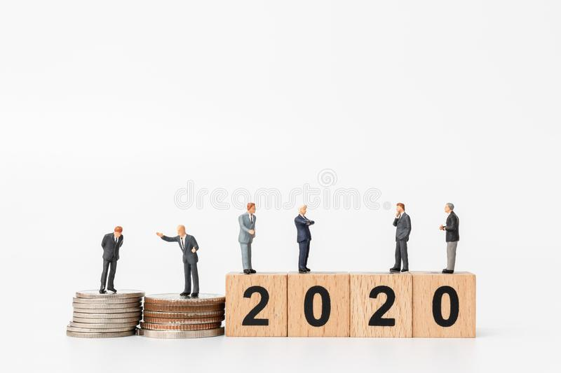 Miniature people : Business people standing on wooden block number 2020. Happy new year concept stock images