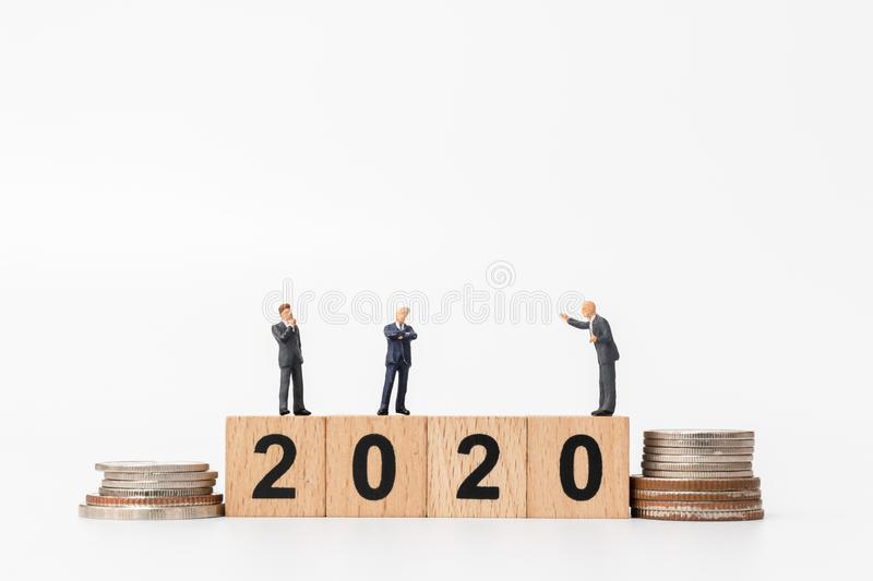 Miniature people : Business people standing on wooden block number 2020. Happy new year concept stock photos