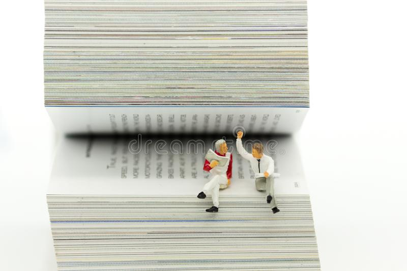 Miniature people: business team reading news paper on book. Image use for background education ,business concept. Miniature people: business team reading news royalty free stock photography