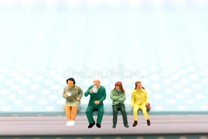 Miniature people : Business team sitting on book and having a coffee break. Image use for business concept royalty free stock photo