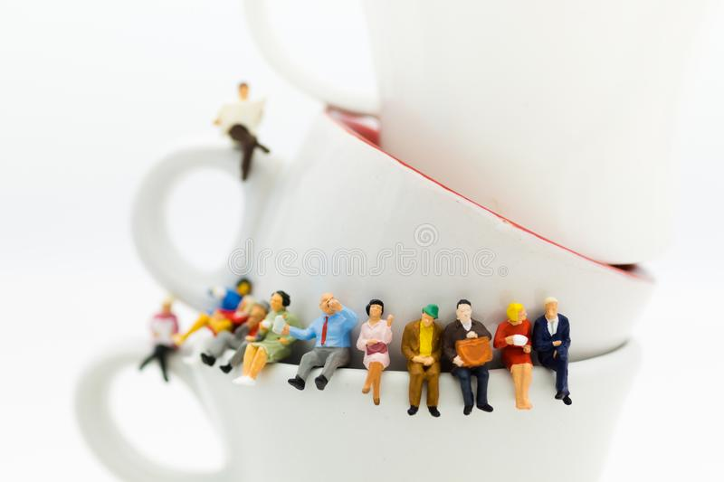 Miniature people : Business team sitting on cup of coffee and having a coffee break. Image use for business concept. stock image