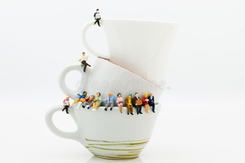 Miniature people : Business team sitting on cup of coffee and having a coffee break. Image use for business concept royalty free stock image